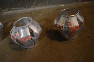 two exploded CM Instantaneous Blast OC Grenade cans from defense technology orange writing on split silver cans. The lids have been completely blown off and the canisters have split along 6 different seems in pre-machined grooves.