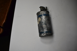 old silver spent grenade can with blue writing and lines but its all banged up and coated with gunk so hard to read