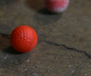 Small dimpled spheres that resemble golf balls are pictured on the ground. Their paint colors vary, but the ones pictured are red and a gradient of white to yellow to Orange to pink and red. These dimples function to make the spheres noticeably more aerodynamic when propelled. They're made of a smooth plastic like substance that appears hard to the touch. Much like a smaller golf ball.